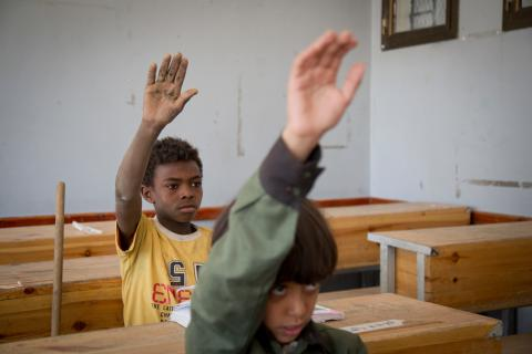Two boys in classoom in Yemen sit at their desks with their hands raised