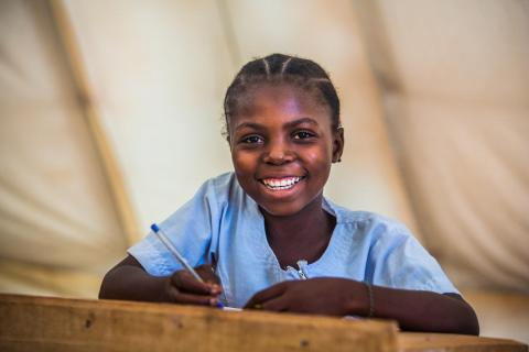 A student in the Democratic Republic of Congo sits at her desk holding a pencil and smiling