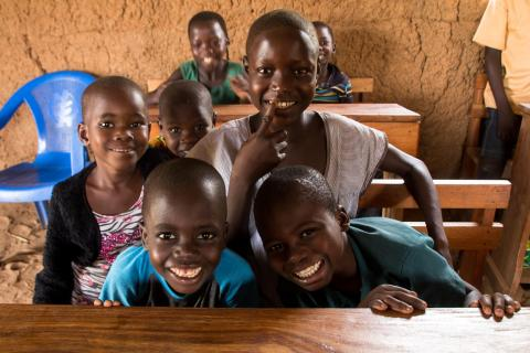 A group of children sitting at desks in a classroom with mud walls smile at the camera