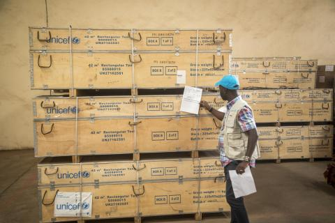 A man waering a blue UNICEF cap examines paperwork infront of an emergency supply shipment