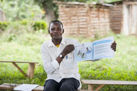 Photograph of a man sitting on a bench holding a UNICEF report in his hands