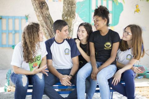 A group of smiling teenagers sitting together on a bench