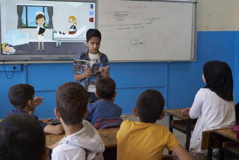 A boy stands in front of his classmates reading from a book with a tv screen and whiteboard behind him