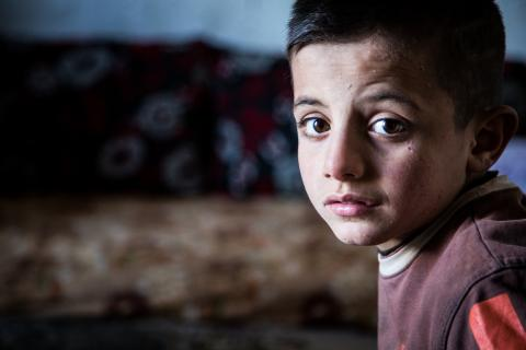 A young Syrian boy sitting in his flat in Lebanon.
