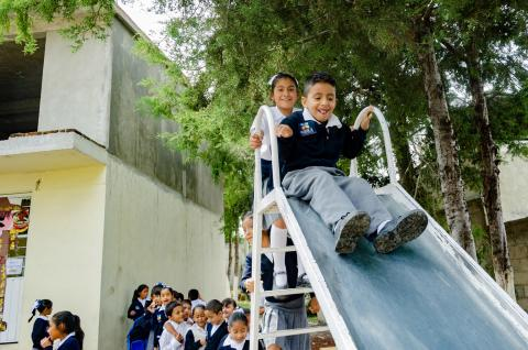 Children playing on a slide in a school playground