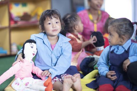 A young girl sitting on the floor of a kindergarten holding a doll with other children and a teacher in the background