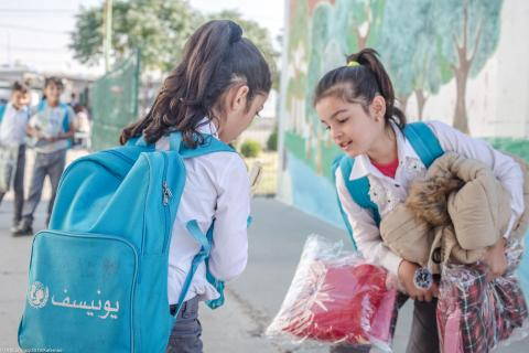 Two young schoolgirls wearing UNICEF schoolbags stand together in a schoolyard