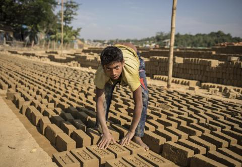 A teenage boy lays bricks out to dry in the sun