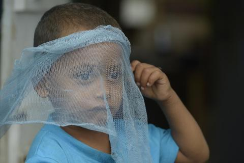 A young boy holding a piece of see through material accross his face