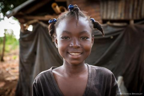 A smiling girl standing in front of her home in Haiti