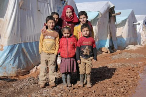 A group of children standing outside their temporary home in the Ared al-Jeb refugee camp in the Syrian Arab Republic.