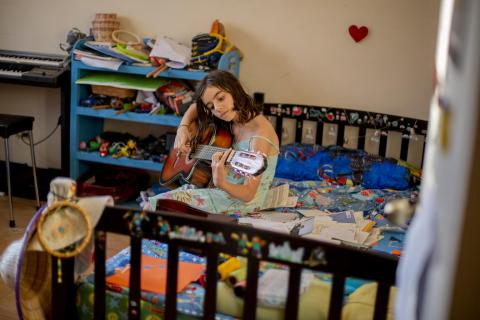 A girl sitting in her bedroom playing her guitar